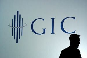 A man is silhouetted against the Government Investment Corporation (GIC) logo .