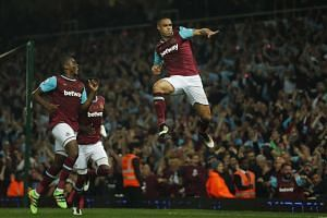 West Ham's Winston Reid (right) celebrates scoring the third goal in the English Premier League football match against Manchester United.