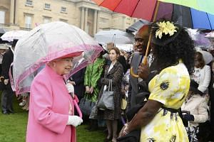 Queen Elizabeth II speaks to Pastor Kofi Banful and Jayne Banful in the garden of Buckingham Palace on May 10, 2016.