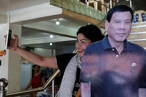 An admirer taking a selfie with a cut-out image of Mr Duterte at a restaurant in Davao city, southern Philippines.