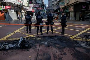Hong Kong policemen cordon off an area next to burnt debris following clashes between protesters and police in Mongkok on Feb 9.
