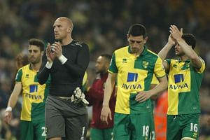 Dejected Norwich players applaud the fans at the end of the match.