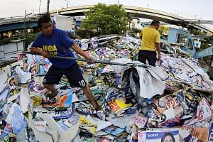 Philippine government workers clearing campaign posters in Manila after Monday's general election. Davao's long-time mayor Rodrigo Duterte won a convincing victory to become the next president of the Philippines, and will take office at the end of ne