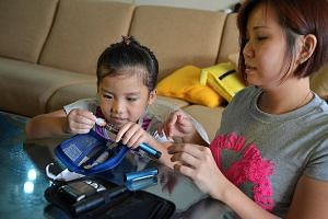 Ms Rosalind Goh teaching her daughter, Romanne Tan (both above), who suffers from Type 1 diabetes, how to change disposable needles. Ms Nurul Jannah Buang (left) was diagnosed with Type 1 diabetes as a teen and had to grapple with eating less chocola