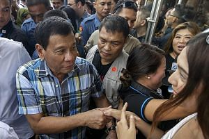 """Mr Duterte (left) greeting supporters yesterday in Davao. The Philippine leader said he would give security forces """"shoot-to-kill"""" orders for organised criminals or those who resist arrest violently."""
