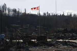 A handout picture made available by the Government of Alberta on May 16,  2016, shows a Canadian national flag flying over a general view of damage caused by a wildfire that swept through several neighbourhoods in Fort McMurray, Canada.