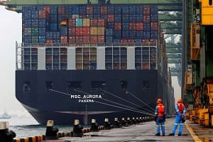Workers looking as a container ship is unloaded at a berth in Singapore.