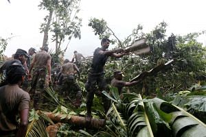 Sri Lankan military rescue team clears the rubble from a landslide site at Elangipitiya village in Aranayaka, Sri Lanka, on May 19, 2016.