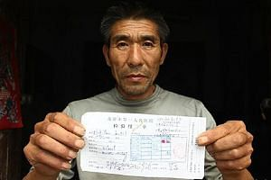 Mr Yang holding up a diagnosis report which confirms that he does not have HIV, the virus which causes Aids. He was deserted by his wife and children, lost his job and ruined his health as a result of the misdiagnosis in 2004.