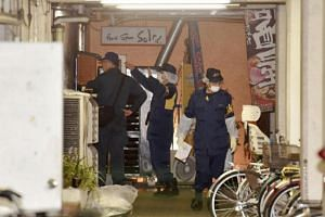 Police forensic investigators gathering evidence near where Japanese pop star Mayu Tomita was attacked by a fan, in Koganei, Tokyo, on May 21, 2016.