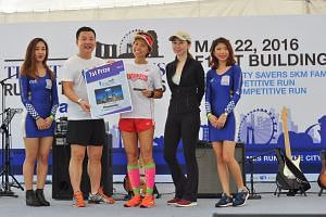 Jasmine Goh (centre) of Singapore accepts the first prize award in The Straits Times Run in the City Women's 10km category.
