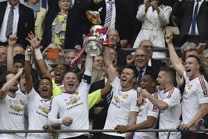 Manchester United's Wayne Rooney and Michael Carrick lift the trophy as they celebrate winning the FA Cup.