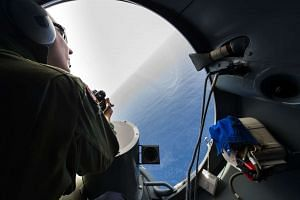 A French soldier aboard an aircraft looking out a window during searches for debris from the crashed EgyptAir flight MS804 over the Mediterranean Sea on May 20, 2016.