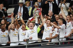 Manchester United captain Wayne Rooney (centre) and his teammates celebrating after winning the English FA Cup final between Crystal Palace and Manchester United, on May 21, 2016.