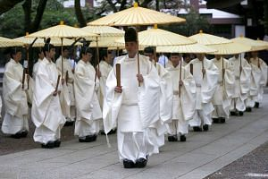 Shinto priests holding traditional umbrellas during a ritual to cleanse themselves during the annual Spring Festival in Tokyo on April 21, 2016.