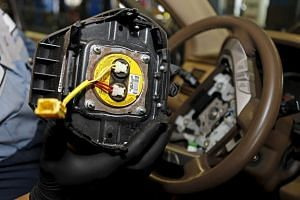 A technician holds a recalled Takata airbag inflator in Miami, Florida, on June 25, 2015.