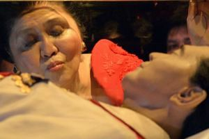 Former Philippine first lady Imelda Marcos kissing the glass case bearing her late husband and former president Ferdinand Marcos, on July 2, 2014.