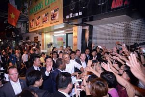 US President Barack Obama (centre) shakes hands with residents as he leaves a restaurant which serves bun cha - a traditional Vietnamese dish of noodle and grilled pork - in Hanoi on Monday.