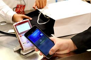 A man making a purchase at Uniqlo fashion store in One Raffles Place using Apple Pay with his iPhone 6s Plus.