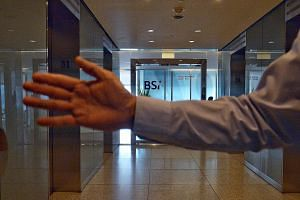 A staff member blocking the media from taking photographs of BSI Bank's main office at Suntec Tower One. BSI Singapore said it is operating normally and working to ensure a smooth and quick integration with EFG.