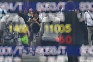 Pedestrians reflected on an electronic stock board at a securities company in Tokyo on May 25.