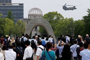A Japan Self-Defense Force CH-47 helicopter flies over the Atomic Bomb Dome at Peace Memorial Park in Hiroshima, Japan, on May 27, 2016.