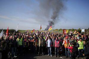 Labour union employees stand near a burning barricade before a police operation to free up a fuel depot near the Donges oil refinery, in Donges, France, on May 27, 2016.