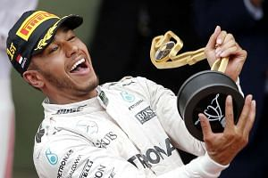 Lewis Hamilton of Mercedes AMG GP celebrates on the podium with the trophy after winning the Monaco Formula One Grand Prix in Monaco, on May 29, 2016.