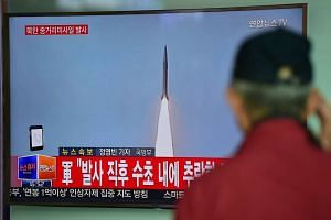 A man watches a TV news showing file footage of a North Korean missile launch, at a railway station in Seoul on April 28, 2016.