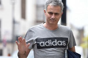 Jose Mourinho gestures as he walks towards his house in London.