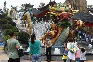 Visitors take photos beside a dragon fountain at the Wanda Cultural Tourism City in China on May 28, 2016.
