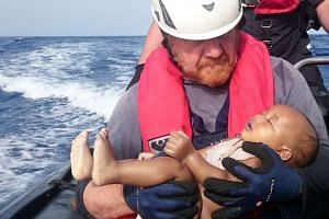 German rescuer from the humanitarian organisation Sea-Watch holds a drowned migrant baby, off the Libyan coast, on May 27, 2016.