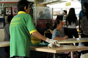 A cleaner clearing away dirty dishes at an Ang Mo Kio coffee shop..