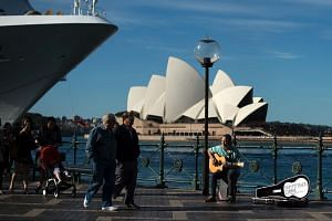 A man plays a song on a guitar on the Sydney Harbour in front of iconic Sydney Opera House.
