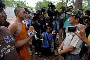 A Thai wildlife official speaks with a monk before officials removed tigers from enclosures at the Wat Pha Luang Ta Bua Tiger Temple, on May 30, 2016.