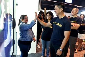 Minister Tan Chuan-Jin exchanging high fives with Ms Chen Wanyi, who has Down syndrome. Behind her is an interactive bus stop ad. If anyone high-fives her image in the ad, she would introduce herself and do a short dance. The bus stop ads are part of