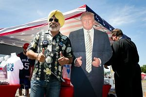 A Trump supporter posing with a cardboard standee of the presidential candidate. The July 18-21 convention is shaping up to be another reminder of the disarray and disunity in the Republican Party.