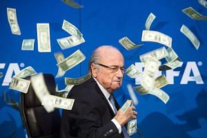 A file picture dated 20 July 2015 of then Fifa president Joseph Blatter reacting while banknotes thrown by British Comedian Simon Brodkin hurtle through the air during a press conference following the extraordinary Fifa Executive Committee at the Fif