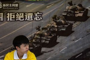 "An activist sits in front of a poster of the ""Tank Man"" photo at his stall in Hong Kong on June 4, 2016."