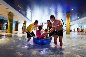 A family having fun at an indoor water playground.