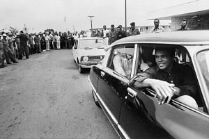 A 1974 photo shows Ali being welcomed by a cheering crowd in Kinshasa, Zaire.