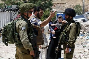 Members of a Palestinian family stand near Israeli soldiers at a checkpoint after the Israeli Army announced the area as a closed military zone, on June 9, 2016.
