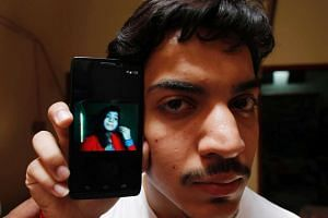 Hassan Khan shows the picture of his wife Zeenat Bibi, who was burnt alive by her mother, on his cellphone at his residence in Lahore on June 8, 2016.