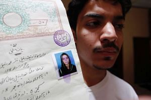 Hassan Khan shows a document with a photograph of his wife Zeenat Bibi, who was burnt alive by her mother, at his residence in Lahore, on June 8, 2016.