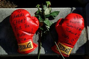 Boxing gloves with well wishes are left at a makeshift memorial for late boxing champion Muhammad Ali in Louisville, Kentucky on June 8, 2016.
