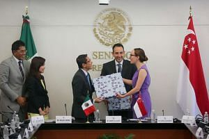 Minister of State for Foreign Affairs and Defence Maliki Osman and Mexican senator Gabriella Cuevas Barron exchanging gifts on June 8, 2016.