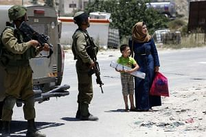 Israeli soldiers talk to Palestinians in the village of Yatta in the occupied West Bank on June 9, 2016, in search for clues leading to an attack the previous night in Tel Aviv.