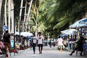Tourists walk past market stalls next to a beach near Pattaya in Thailand.