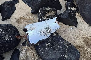 A picture released on May 27 by the Mauritius National Coastguard shows a piece of aircraft debris, suspected to be part of the missing flight MH370, found at the Gris Gris public beach near Souillac, Mauritius, on May 24.
