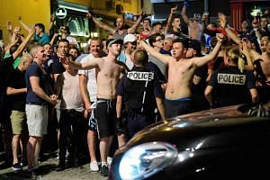 Police stand guard as England fans gather and chant slogans in the port area of Marseille, late on June 9, 2016.